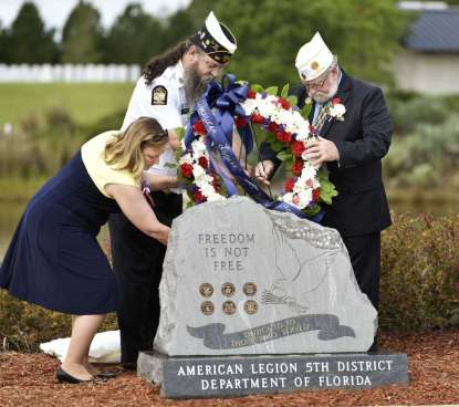 Will.Dickey@jacksonville.com Kelli Becraft (from left), Walter Rasco and Joe Magee lay a wreath during the dedication of the American Legion Family Monument at the Jacksonville National Cemetery.