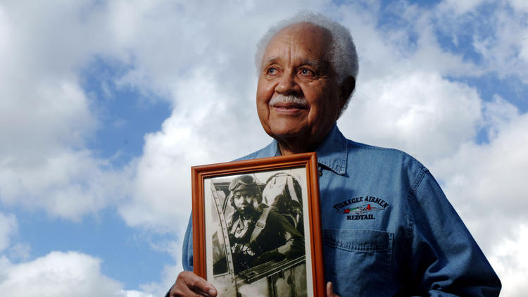 Retired Lt. Col. Leo Gray, 82, a retired Tuskegee Airman, holds a 1945 photo of himself after flying a mission over Europe. Gray is one of 300 who will were awarded the Congressional Gold Medal by President Bush on March 29 in Washington, D.C. Susan Stocker, Sun Sentinel